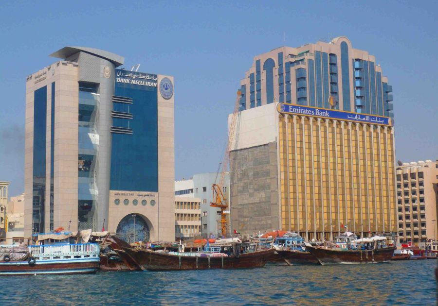 From a boat on the water. Old boats in front of modern buildings.