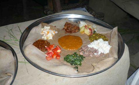Injera under several different Ethiopian foods.