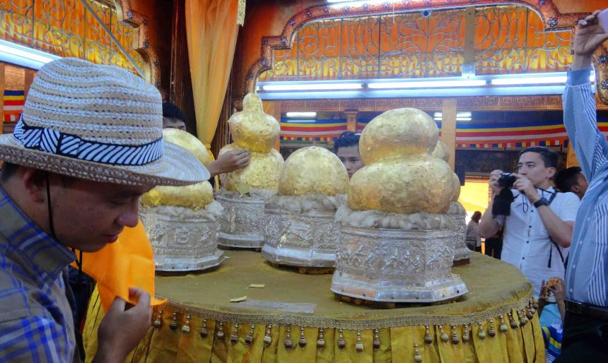 Temple on Inle Lake, people add gold leaf to statues that once were Buddhas.