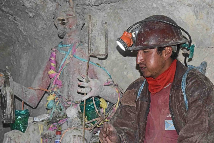 Our guide with a statue of the mine's God, Tio.