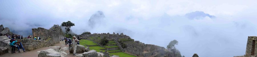 Machu Picchu looks out to many mountains, hideen by the clouds.